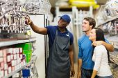 friendly african hardware store assistant helping young couple choosing taps