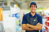 happy young salesman standing in hardware store