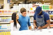 happy couple choosing paint color at hardware store with help of the shop assistant