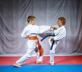 Two small athletes are training paired exercises karate
