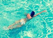 The sporting woman swims in bright blue waterwith a retro effect