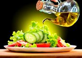 Healthy Vegetable Salad with Olive oil dressing. Pouring Olive oil. Healthy vegetarian food. Vegan.