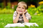 Beauty Smiling Child Boy Reading Book Outdoor On Green Grass Field