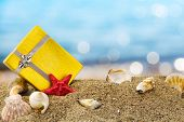 pic of money prize  - Gold gift box on sand with summer sea background - JPG