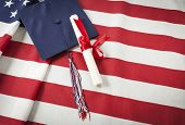 image of tassels  - Graduation Cap with Tassel and Red Ribbon Wrapped Diploma Resting on American Flag - JPG