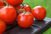 Lovely fresh small red tomatoes on the vine. Sitting on a dark wood table with out of focus grass in