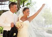 Happy couple on wedding-day, bride posing in wedding gown holding long veil.
