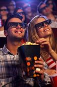 Young couple sitting in auditorium of multiplex movie theater, watching 3D movie, eating popcorn, sm