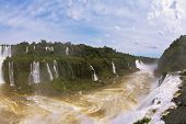 Raging and roaring water in the Brazilian side of the Iguazu Falls.  Turbid yellow-brown waves flow