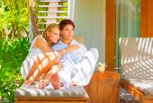 Cute happy couple enjoying outdoors, sitting on sunbed on luxury tropical resort, sunny day, romanti