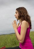 pic of namaste  - Woman is in namaste pose meditating outdoors - JPG