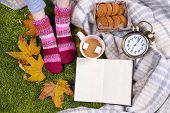 Composition with warm plaid, book, cup of hot drink and female legs, on color carpet background