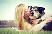 stock photo of shepherd dog  - a young caucasian woman with long blonde hair is laying outside hugging and kissing her German Shepherd Dog. Vintage style color.