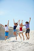 Ecstatic young people holding by hands while jumping over sandy beach