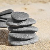 some stacks of stones on the sand of a beach