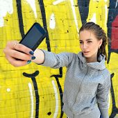 Happy attractive girl with smart phone takes photo of herself against urban grunge graffiti wall