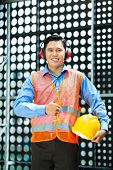 Asian Indonesian construction worker with helmet and safety vest on a building site in Asia