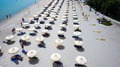 Beach With Tourists, Sunbeds And Umbrellas. Beach Of Kallithea, One Of The Most Visited Destinations