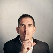 foto of shh  - Close up portrait of adult businessman saying  - JPG