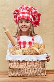 Happy little chef offering fresh bakery products from a basket