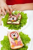 Decorating creative food - creature sandwiches with child hands, closeup