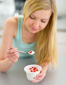 Young Woman Eating Yogurt In Kitchen