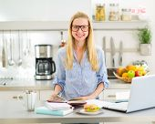 Portrait Of Happy Young Woman Studying In Kitchen