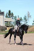 Blonde Woman Riding Black Horse
