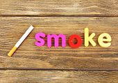 Smoke word formed with colorful letters on wooden background