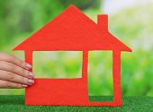 Woman hand holding paper house on grass on bright background