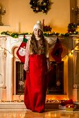 Girl Standing In Santa Red Bag At Living Room Next To Fireplace