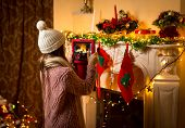 Cute Girl Making Photo Of Decorated Christmas Fireplace On Digital Tablet