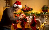 Young Father Putting Gifts In Christmas Stockings At Fireplace