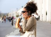 Young Woman Talking On Mobile Phone And Eating Outdoors