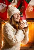 Brunette Woman In Woolen Sweater Holding Vaporing Cup At Fireplace