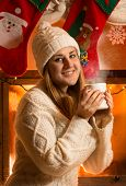 Portrait Of Beautiful Woman In Woolen Sweater Drinking Tea At Fireplace
