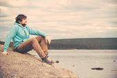 stock photo of swag  - Young Man Traveler relaxing alone outdoor Lifestyle concept with mountains and lake on background - JPG