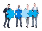 Group of Business People Holding Puzzle Pieces