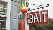 Bait shop sign hang from wall with fishing buoys.