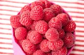 Beautiful raspberries  in a pink bag on a striped background