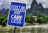 Don't Be Careless Just Care Less sign with a forest background