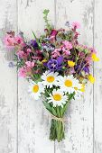 Wild flower posy over distressed wooden background.