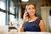 Happy young woman eating sushi in a restaurant and using mobile phone