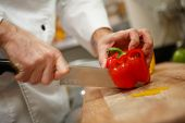 closeup on hands cutting yellow pepper on professional kitchen