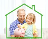 family, children, money, investments and happy people concept - happy father and daughter with big pink piggy bank behind green house symbol