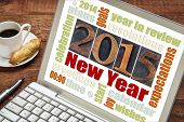 2015 New Year concept - word cloud on a laptop screen with a cup of coffee