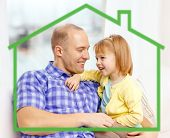 family, childhood, ecology and happiness concept - smiling father and daughter together at home behind green house symbol