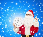christmas, holidays and people concept - man in costume of santa claus with clock showing twelve pointing finger up over blue snowy background