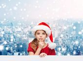 christmas, holidays, childhood and people concept - smiling little girl in santa helper hat with finger on her lips over snowy city background