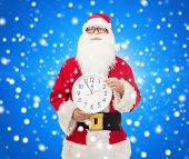 christmas, holidays and people concept - man in costume of santa claus with clock showing twelve pointing finger over blue snowy background